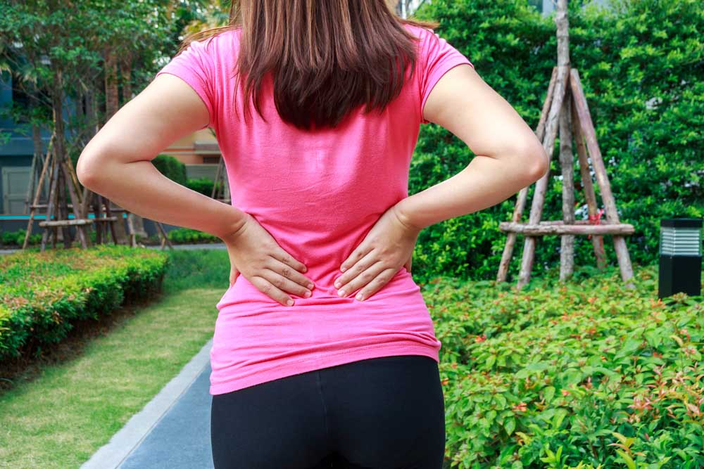 Woman with back pain in Mableton, needs chiropractic care.